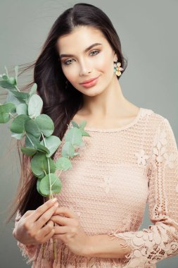 Cheerful woman fashion model with green leaves. Happy girl with long hair and makeup