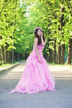 Beautiful woman in pink dress in park