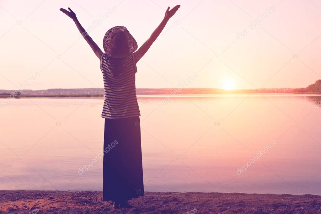 girl in hat meeting sunrise in morning with spreading hands