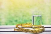 Fotografia Bicchiere di acqua naturale pura e giallo nastro di misurazione su sfondo naturale, simbolo di salute e dieta
