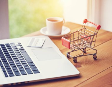laptop with credit card and trolley as symbol of online shopping and paying