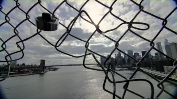 Pohled na New York nábřeží a Brooklynský most přes poškozený plot