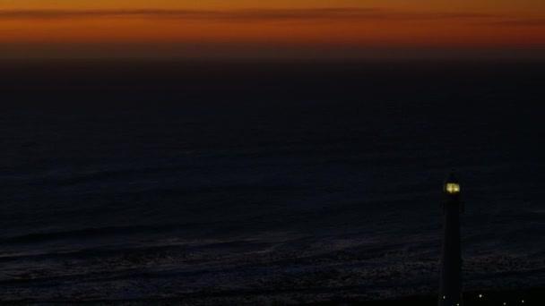 Výhled na maják a oceán jako vlny zasáhnout pobřeží v noci
