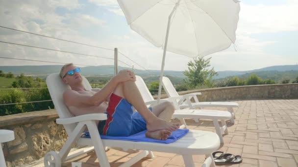 Egy ember ül a medence rajta kék nadrág és árnyalatok, miközben nézi a kamerát