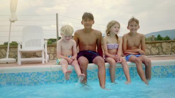 Čtyři děti jsou šťastně namáčení nohou do fondu.