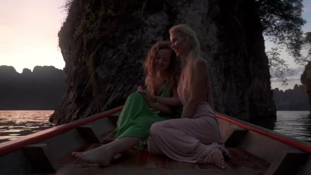 Focused shot on women holding hands as canoe slowly turns towards the sunset.