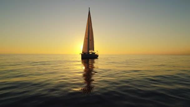 Vzdušné straně střílel z plachetnice, zatímco slunce pomalu zapadá nad obzorem.