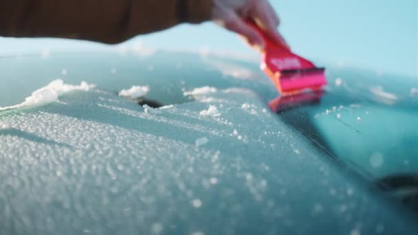 Egy férfi egy piros kaparóval Használja az autó szélvédőjét, hogy eltávolítsa a jeget