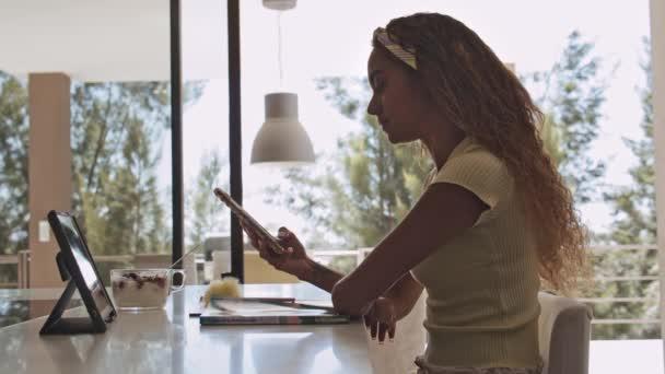 Schöne Studentin blättert beim Online-Studium durchs Telefon
