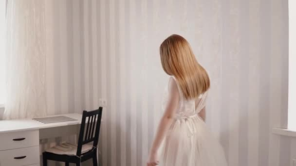 Die Braut in eine Frisiermantel sieht und berührt eine Hochzeitskleid
