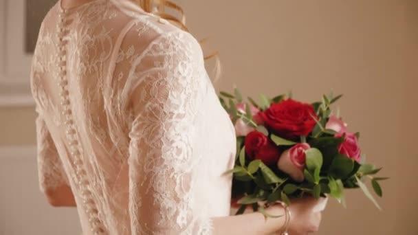 Blonde nevěsta ve svatebních šatech s květinami pózuje pro kamery