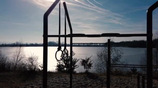 Silhouette of workout gym in nature on beach near lake.