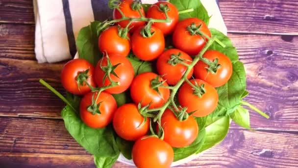 HD video rotace z čerstvých červených rajčat leží na čerstvý špenát jsou na dřevěný stůl.