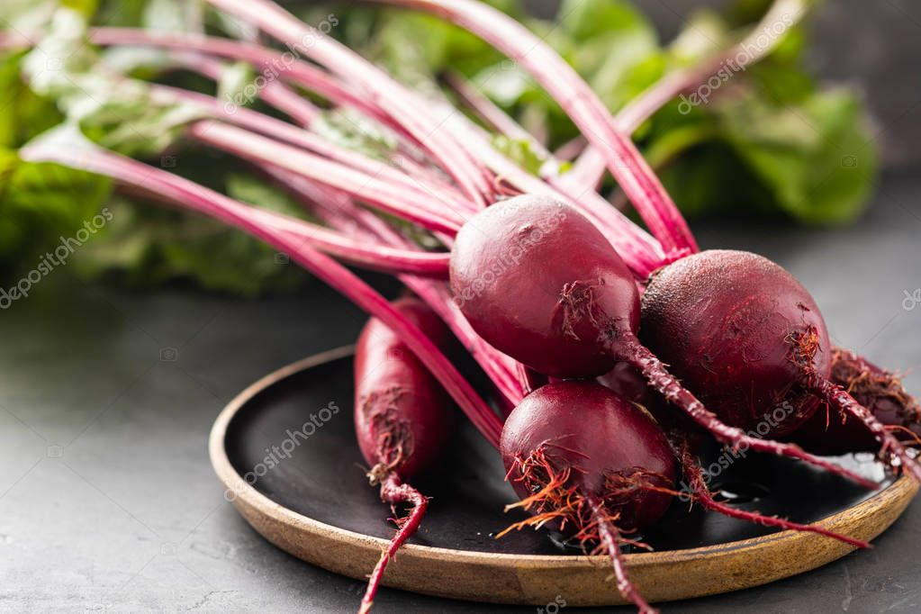 Beet, beetroot bunch on wooden plate on grey stone background. Copy space. .