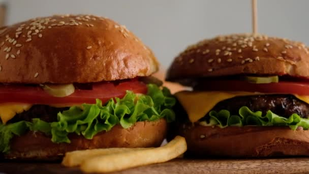Rychlé občerstvení. Makro pohled na hamburgery, hranolky, colu. Žena udělala hamburger z housek, řízků, salátu, okurek, rajčat, cibule a omáček. Krásné pozadí. Zpomalený pohyb.