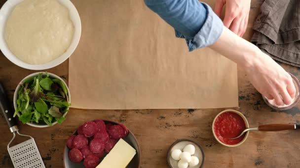 Pohled shora, ženské ruce nalít mouku a dát těsto, připravit italskou pizzu s omáčkou, rajčata, koření, feronkové klobásy, špenát, zelenina, sýr mozzarella. Těsto na chleba. Pizza pepperoni.