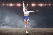 Fényképek Beautiful asian cheerleader in action with spotlights on background