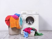 Laundry basket and washing machine at home. Home appliances