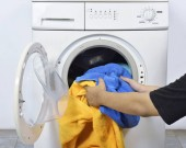 Muž načítání špinavé ručníky do pračky pro prát v domácnosti