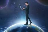 Asijský podnikatel přenosném počítači při chůzi na zemi s pozadím vesmíru
