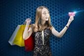 Fényképek Szép ázsiai nő a bevásárló szatyrok mutatja a hitelkártya-át digitális kék háttér. Cyber hétfő koncepció