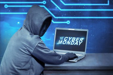 Hacker using laptop with text cyber monday on the screen. Cyber monday concept