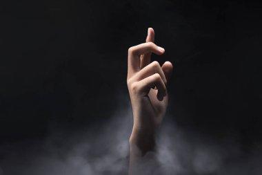 Hands finger with cross gesture over dark background. Christian Pray