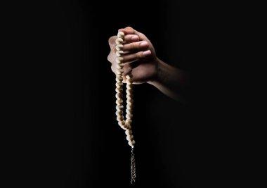 Male hands praying using prayer beads over dark backgroud. Muslim Pray