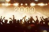 Silueta lidí slaví Nový rok s 2019 a létající konfety. Šťastný nový rok 2019