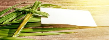 Closeup view of cross shape of palm leaf and palm branches with white blank paper and ray in wooden background. Palm Sunday concept