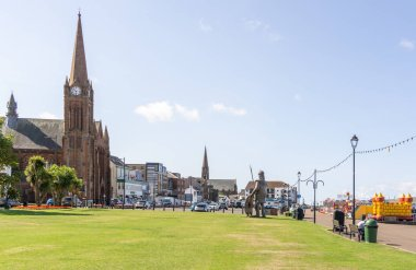 Largs, Scotland, UK - July 19, 2018: Looking along Gallowgate street into the Largs town centre on a record breaking hot summers day. Magnus viking warrior seen in the foreground.