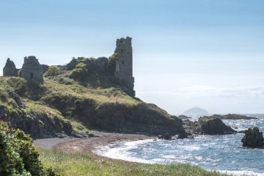 The ancient ruins of Castle Dunure with Ailsa Craig in the hazy distance taken on a warm  hazy sunny day and is a good image for Scotland's tourism.