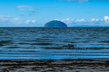 Ailsa Craig on a cold Septembers day with dark cold water and blue skys