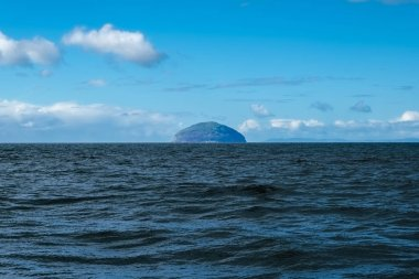 A cold blue sea with Ailsa Craig at the centre of the image under a cold blue sky in September.