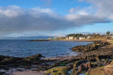 The town of Largs set on the Firth of Clyde on the West Coast of Scotland. Looking along the rocky lichen covered foreshore to the tow of Largs which can be seen in the far distance. A good touristic image.