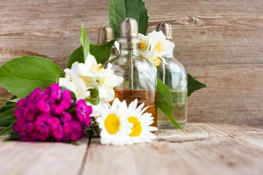 Spa perfume essential aroma oil glass bottles with flower blossoms on old wooden background