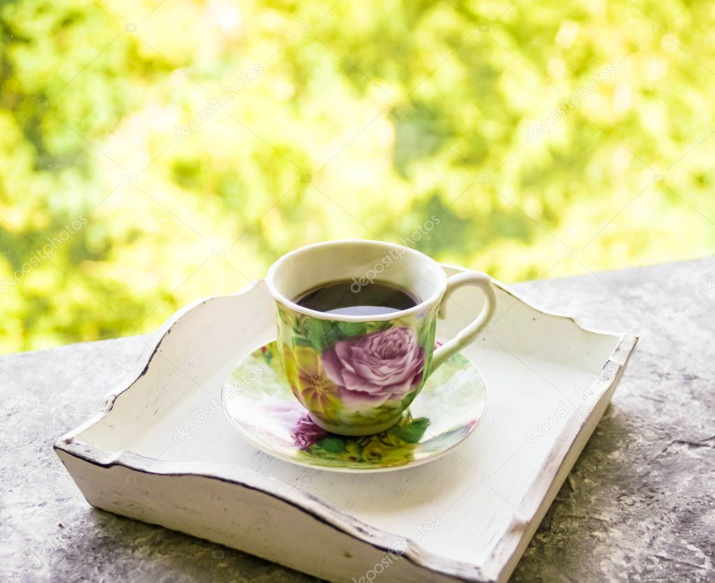 Hot morning coffee in small floral design cup on shabby chic vintage white tray on window sill in front of summer window