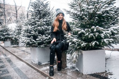Beautiful russian girl in a cloud day in winter style clothes, walking in Tverskaya Square in Christmas time