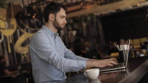 Man with a laptop at a table in a restaurant or bar, man working on laptop in cafe, Young hipster man having a coffee break at the bar, he is holding a cup and connecting with a laptop, businessman