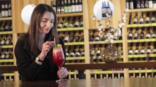 Mladá dívka pije koktejl na stole v módní restauraci, mladá dívka s červeným exotického koktejlu u stolu v restauraci nebo bar, Žena pití červeného exotického koktejlu