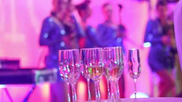 Glasses with champagne on the background of silhouettes of womens music  group, a female music band performs in a restaurant or hotel lobby