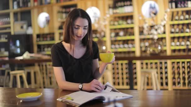 Mladá dívka v restauraci s šálkem čaje, aroma a chuť kávy se těší při odpočinku v kavárně. Mladá krásná šťastná usmívající se dívka drží hrnek s horkým čajem