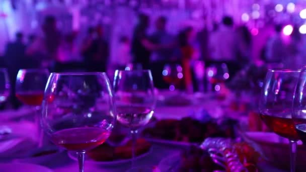 A youth party in a restaurant or a nightclub, banquet tables with alcohol and food against the background of silhouettes of dancing people, stage light and purple fill, shallow depth of field