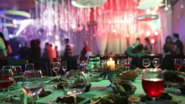Slavnostní stůl v restauraci s brýlemi a svíčku. Lidé tancují na pozadí tabulky. Slavnostní stůl, lidé tančí na pozadí