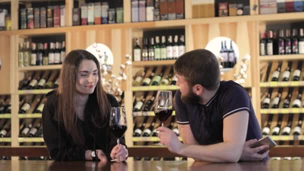 A girl and a guy in a restaurant communicate and drink red wine, a young couple drinks red wine at a table in a restaurant or cafe
