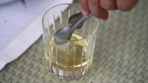 A pincér hozza jeget egy üveg whisky, egy pohár whiskyt az asztalra, egy pohár whiskyt feküdt jégkocka, egy pohár whiskyt jéggel az asztalon