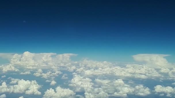 view from the airplane window to the blue sky and white clouds on a sunny day, lots of white clouds float above the earth, a view of the earth through white fluffy clouds