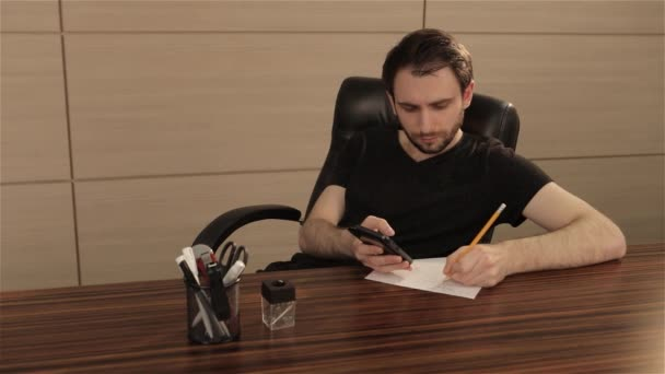 A young man is working at a table in the office. A businessman writes and draws on a sheet of white paper. A young businessman sits at the office desk and makes notes and drawings on a white sheet