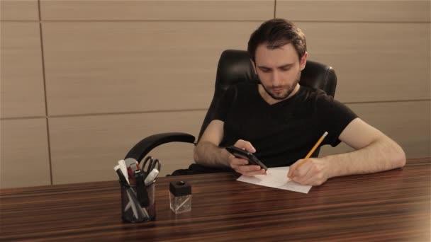 Mladík pracuje u stolu v kanceláři. Podnikatel píše a kreslí na list bílého papíru. Mladý podnikatel sedí na kancelářský stůl a dělá poznámky a kresby na bílý list