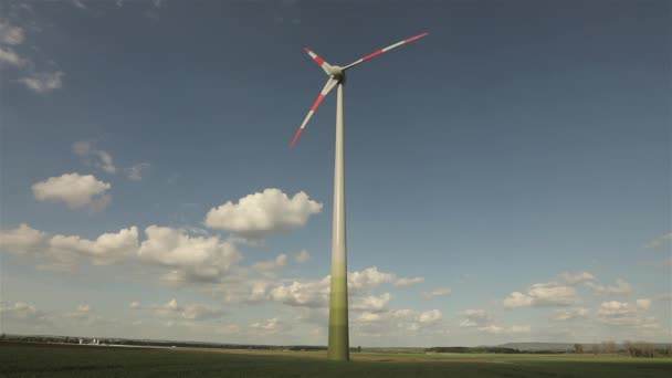 Wind generator against the background of clouds floating in the sky   Rotation of the large wind generator blades  Panoramic view of the  agricultural landscape  Sunny day  Europe  Timelapse